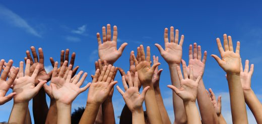 Hands in the air with a blue sky background